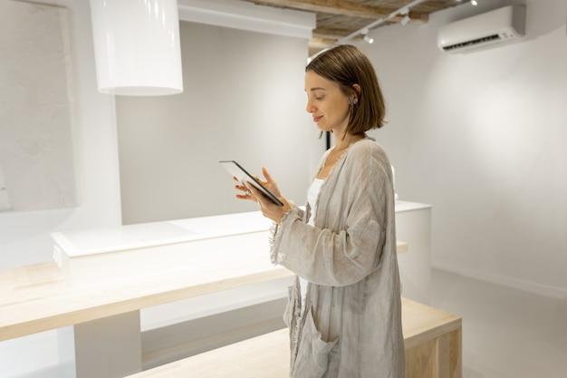 Kobieta komunikuje się w domu za pomocą cyfrowego tabletu