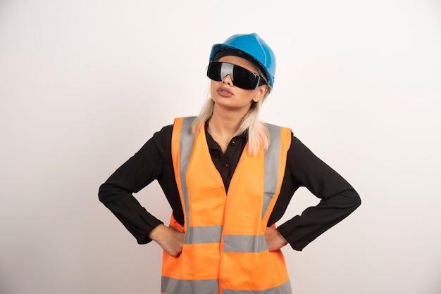 Kobieta konstruktor pozuje z gogle i kask. wysokiej jakości zdjęcie