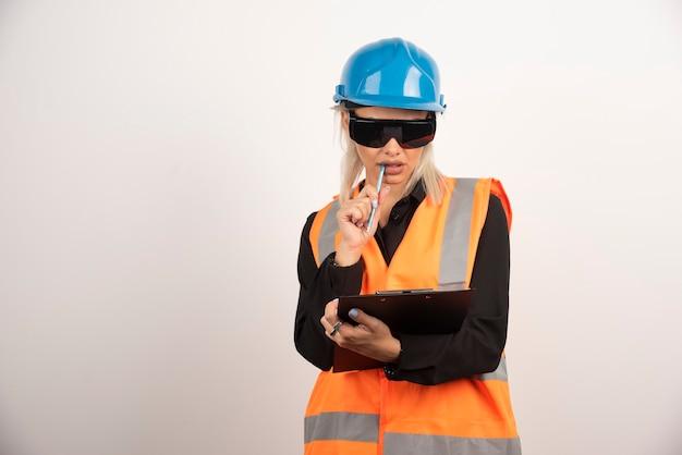 Kobieta konstruktor trzyma schowek z goglami. wysokiej jakości zdjęcie