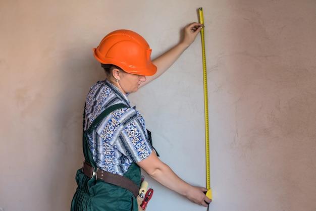 Kobieta konstruktor w jednolitej ścianie pomiarowej z taśmą