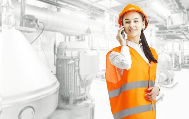 Kobieta konstruktor w pomarańczowym kasku stojąc przed ścianą przemysłową z telefonem komórkowym