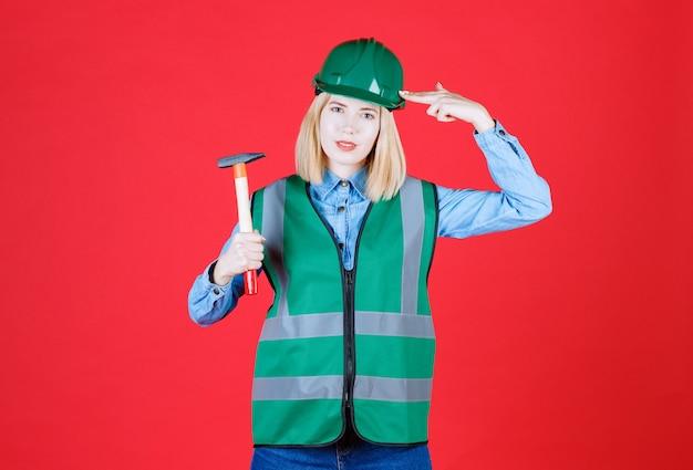 Kobieta konstruktor w zielonym hełmie i mundurze robiącym broń przy głowie trzymając młotek