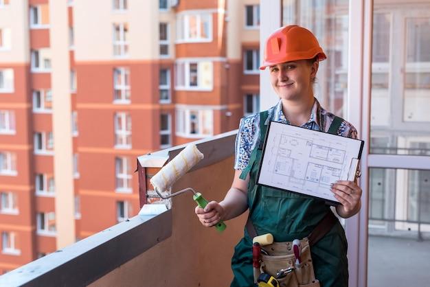 Kobieta konstruktor z planem mieszkania pozuje na balkonie