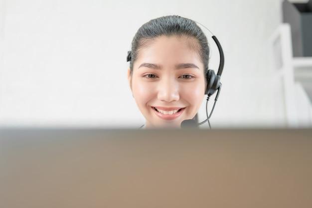 Kobieta konsultant jest ubranym mikrofon słuchawki słuchawki obsługi klienta telefonu operator przy miejscem pracy.
