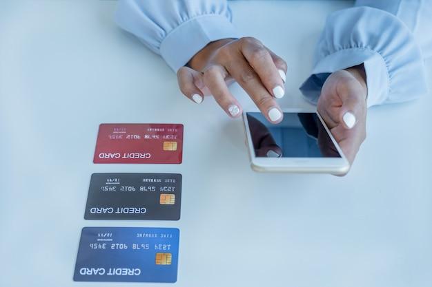 Kobieta konsumenta korzysta ze smartfona i makiety karty kredytowej, gotowej do wydawania pieniędzy na zakupy online
