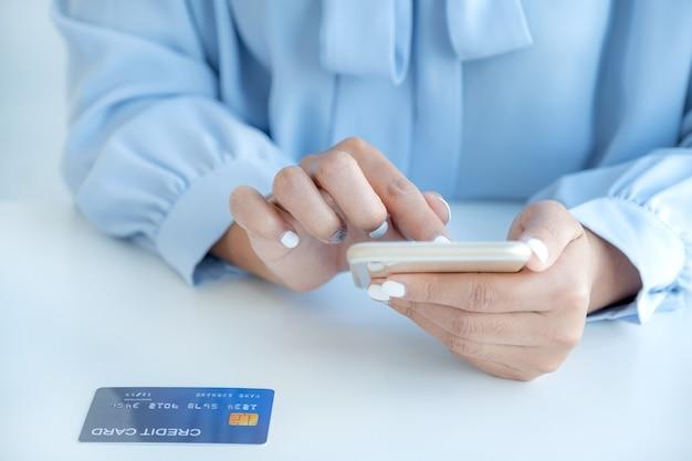 Kobieta konsumenta korzysta ze smartfona i makiety karty kredytowej gotowej do wydawania pieniędzy na zakupy online