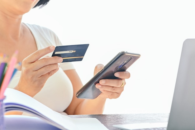 Kobieta korzysta z karty kredytowej do zakupów online na smartfonie i laptopie, robi zakupy w domu, skupia się na karcie kredytowej