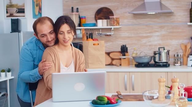 Kobieta korzysta z laptopa w kuchni, podczas gdy jej mąż ją przytula. mąż i żona gotowanie żywności przepis. szczęśliwy zdrowy styl życia razem. rodzina szukająca posiłku online. zdrowa świeża sałatka