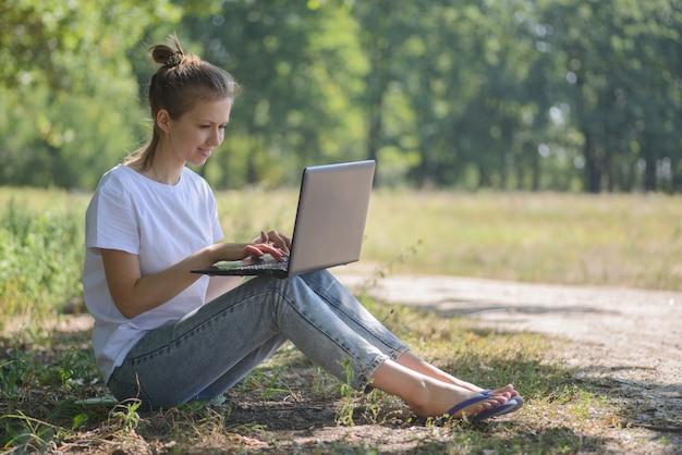 Kobieta korzysta z laptopa w przyrodzie