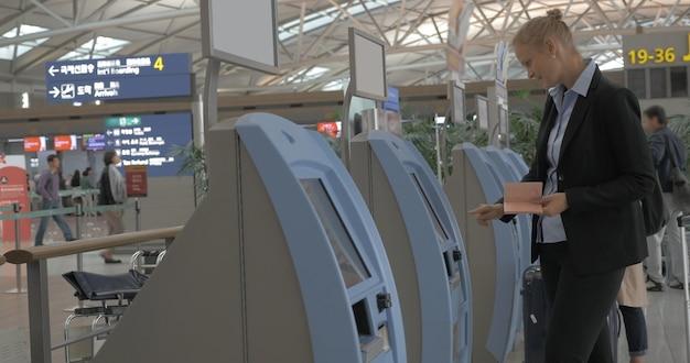 Kobieta korzystająca z automatu samoobsługowego do odprawy