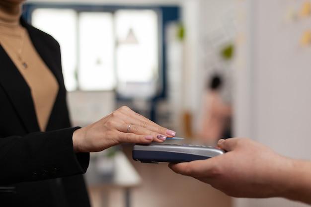 Kobieta korzystająca z koszyka kredytowego z zbliżeniowo przez pos, płacąc za lunch w biurze firmy