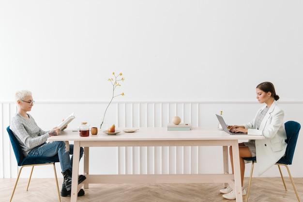 Kobieta korzystająca z laptopa w poprzek kobiety, która czyta książkę