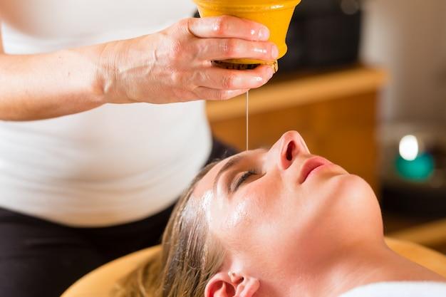 Kobieta korzystająca z masażu olejkiem ajurwedyjskim