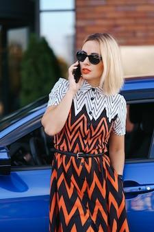 Kobieta korzystająca z telefonu komórkowego, komunikacji lub aplikacji online, stojąca w pobliżu samochodu na ulicy miasta lub parkingu, na zewnątrz. udostępnianie samochodów, wypożyczalnia