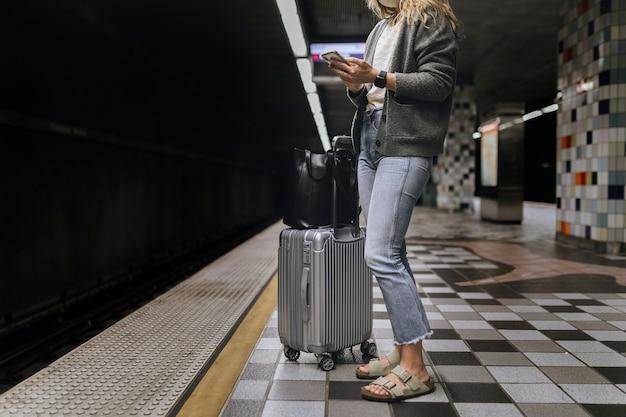 Kobieta korzystająca z telefonu komórkowego podczas oczekiwania na pociąg podczas pandemii koronawirusa