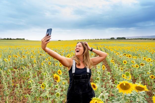 Kobieta korzystająca z telefonu komórkowego wśród słoneczników.