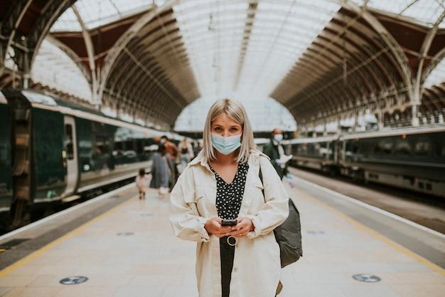 Kobieta korzystająca z telefonu na stacji kolejowej