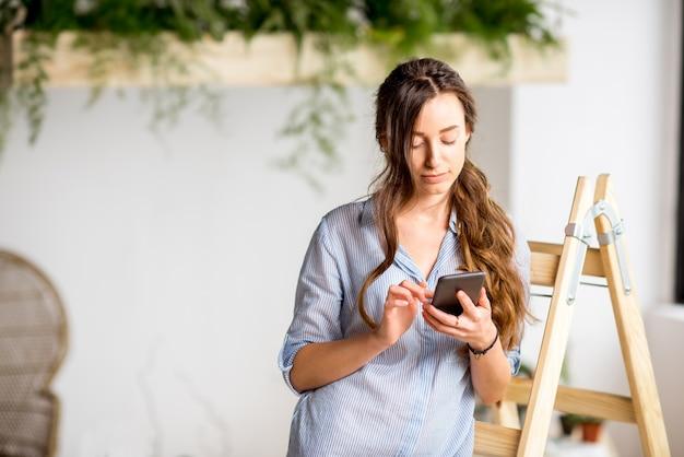 Kobieta korzystająca z telefonu stojącego na drabinie w domu z zielonymi roślinami