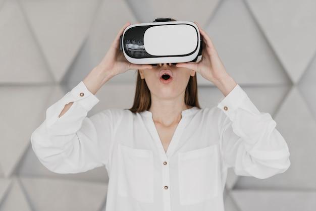 Kobieta korzystająca z zestawu słuchawkowego wirtualnej rzeczywistości i zdumiona