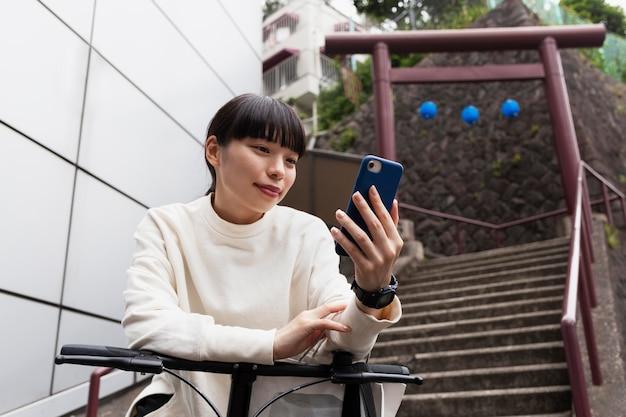 Kobieta korzystająca ze smartfona i roweru elektrycznego w mieście