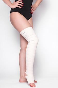 Kobieta kostki na białym tle przeciągnęła elastyczny bandaż
