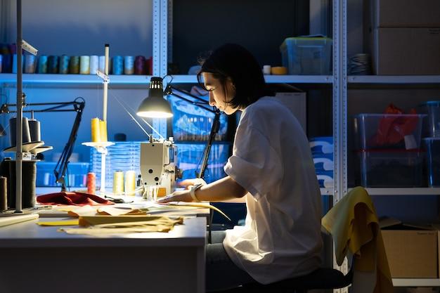 Kobieta krawcowa pracuje na maszynie do szycia, szyjąc ubrania, tworzy nową kolekcję koncepcji małej firmy