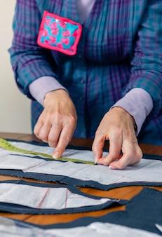 Kobieta krawcowa projekt krawiecki wzór na garnitur na stole