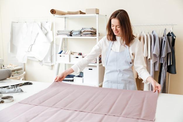 Kobieta krawcowa rozprzestrzenia tkaniny w warsztacie