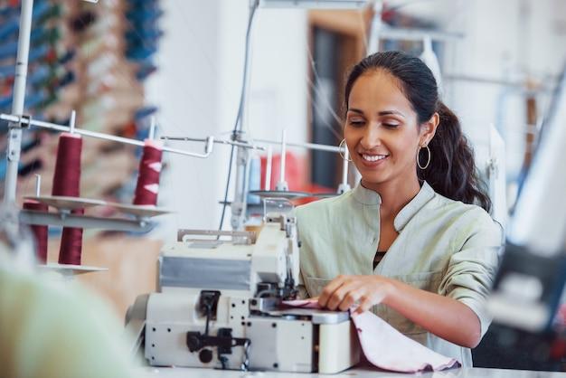 Kobieta krawcowa szyje ubrania na maszynie do szycia w fabryce.