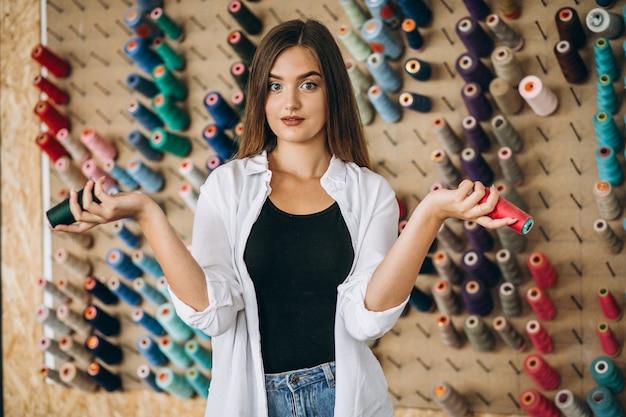 Kobieta krawczyna wybiera nici przy fabryką