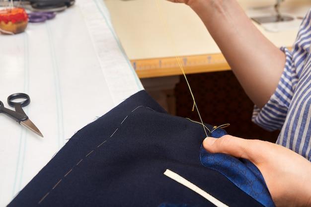 Kobieta krawiec owinięta w szycie kurtkę z igłą i nicią siedząc przy stole roboczym. szycie garnituru w procesie szytego na miarę marynarki. szycie garnituru na miarę.