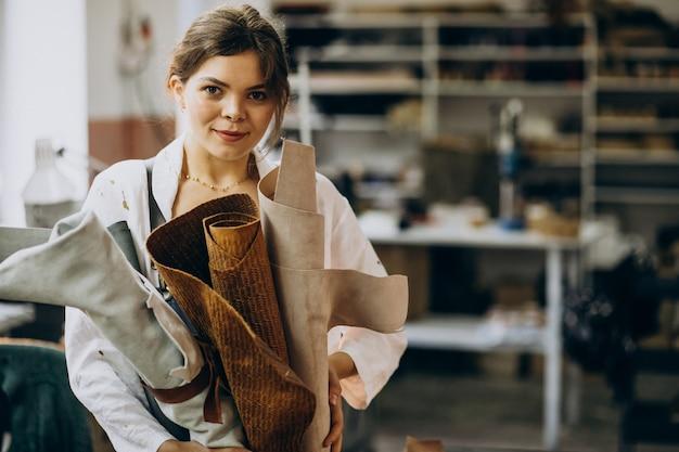 Kobieta krawiec pracujący na skórzanej tkaninie