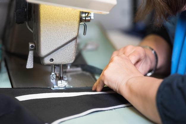 Kobieta krawiec pracuje na maszynie do szycia. ręce. ścieśniać. krawiectwo. detale.