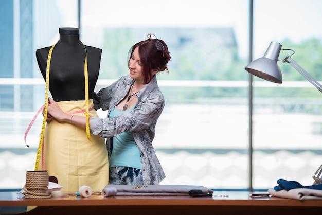 Kobieta krawiec pracuje nad nową odzieżą