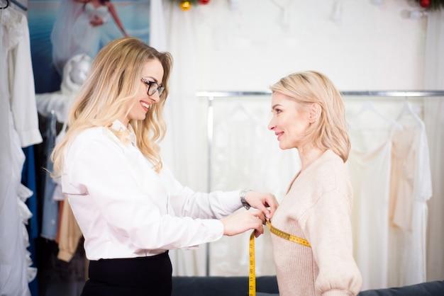 Kobieta krawiec projektant mody przy pomiarze z modelką. koncepcja szyć ubrania.