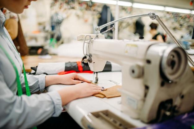 Kobieta krawiec ręce szyje tkaniny na maszynie do szycia
