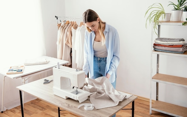 Kobieta krawiec za pomocą maszyny do szycia w studio