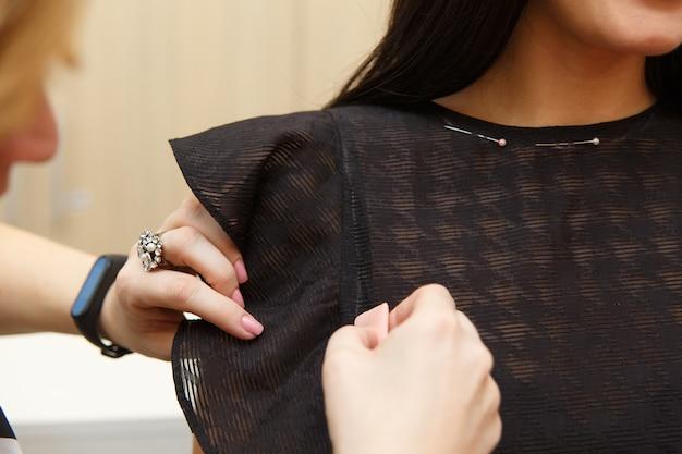 Kobieta krawiecka mierząca rękaw damski uszyta na miarę garnitur dla pięknej klientki w swojej krawcowej