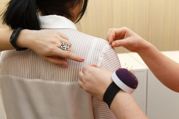 Kobieta krawiecka mierzy kobietę, aby uszyć garnitur na miarę dla pięknej klientki w swojej krawcowej
