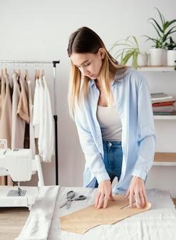 Kobieta krawiecka przygotowuje tkaniny na odzież