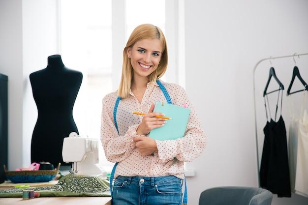Kobieta krawiecka z notatnikiem i ołówkiem w warsztacie