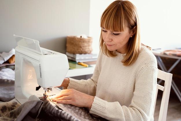 Kobieta krawiecka za pomocą narzędzi do szycia tkanin