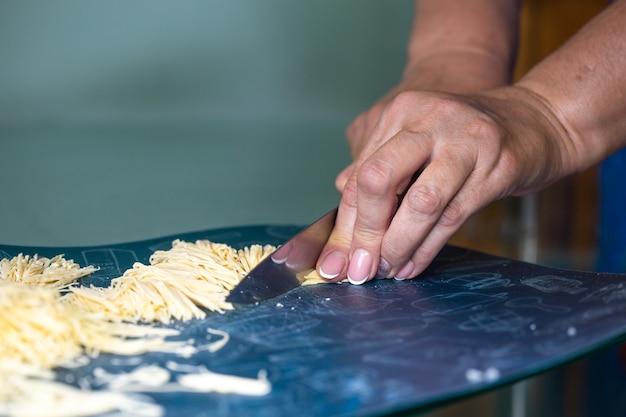 Kobieta kroi domowe kluski w kuchni