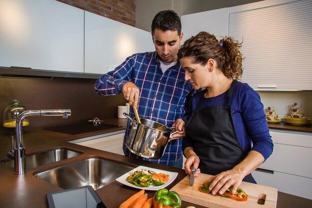 Kobieta kroi warzywa, podczas gdy jej mąż pokazuje jej garnek z jedzeniem