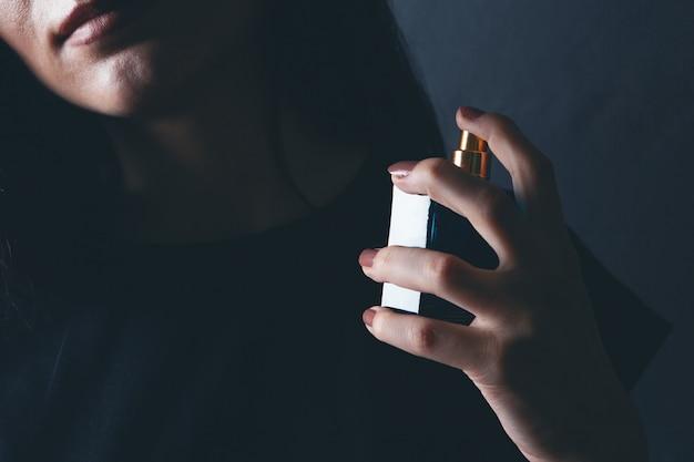 Kobieta kropi perfumy na szyję