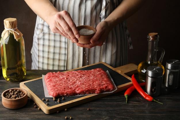 Kobieta kropi sól na mielonym mięsie na drewnianym stole z pikantność, zamyka up