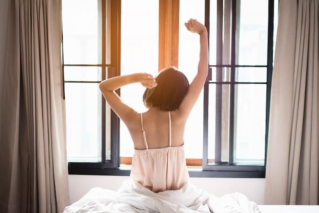Kobieta krótkie włosy rozciągające się w łóżku po przebudzeniu, widok z tyłu