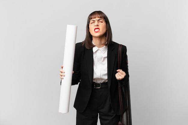 Kobieta krzycząca agresywnie z gniewnym wyrazem twarzy lub z zaciśniętymi pięściami świętująca sukces