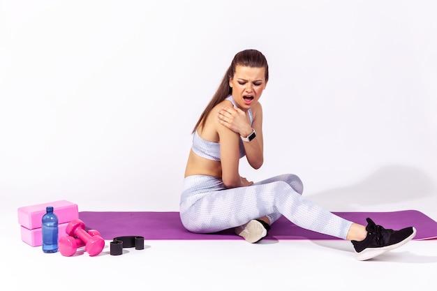 Kobieta krzycząca czuje ból w ramieniu masuje bolący kręgosłup