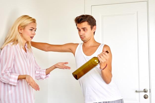 Kobieta krzycząca i obwiniająca mężczyznę alkoholem, kłócą się o jego uzależnienie od alkoholu